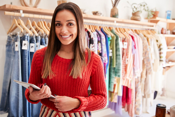Young woman who owns a retail fashion store, wearing a red sweater.